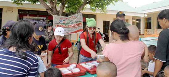 Feeding. Johndorf employees serve some porridge to children in Poro, Camotes.