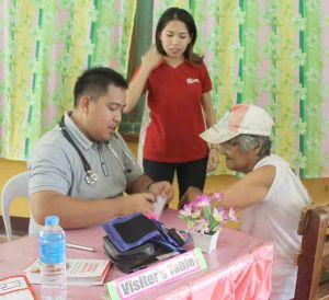 Consultation. A physician attends to an elderly who sought medical attention, while a Johndorf employee assists.