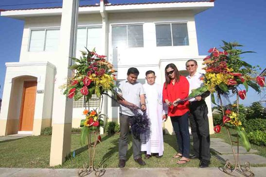 Opal. Homeowner Nimfa Tampus (mid-right) leads the cutting of the ceremonial ribbon with Fr. Raffy de Gracia during the blessing of Phase 6 at Aldea del Sol before the Opal model house. Both are flanked by Filinvest Land, Inc. project development manager Archie M. Igot (left) and area general manager Allan Go Alfon (right).