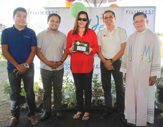 Turnover. Homeowner Nimfa Tampus (center) receives the symbolic key on behalf of her neighbors for their homes at Phase 6 at Aldea del Sol that developer Filinvest Land, Inc. has completed. She is flanked by (from left) subdivision administrator Marc Menina, project development manager Archie M. Igot, area general manager Allan Go Alfon and Fr. Raffy de Gracia, who blessed the new village.