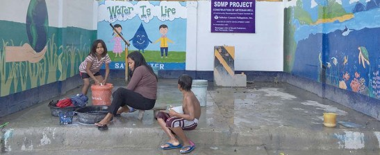 Artesian well. A mother and her daughter do their laundry, while her son takes a bath at the water facility built for them by Taiheiyo Cement Philippines, Inc.  Solid Earth Development Corp. donated the lotto the community.