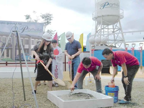 Groundbreaking. Johndorf Ventures Corporation EVP Norma T. Lim shovels some cement to seal the time capsule during the groundbreaking for Portville Prime, as CEO Richard D. Lim await for his turn.