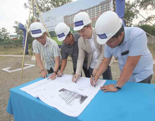Documents. VP/GM Allan Go Alfon, a contractor's representative, AVP sales head Boler L. Binamira, and project development officer Archie M. Igot sign the documents before these are laid inside the time capsule.