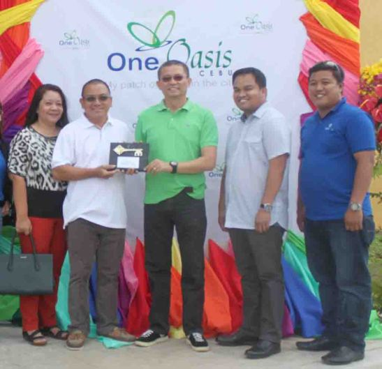 Symbolic Key. Homeowner Alex Alasco and his wife Maria Linda Gutierrez receive from Filinvest Land, Inc. (FLI) area general manager Allan G. Alfon the symbolic key to their unit at the newly-completed Building No. 4 at One Oasis Cebu in Kasambagan, Cebu City.